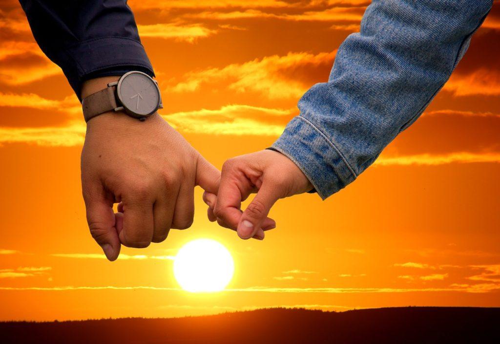 夕日を見ながら手を繋ぐ男女
